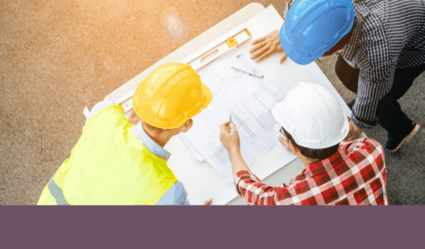 Three construction workers looking over building plans