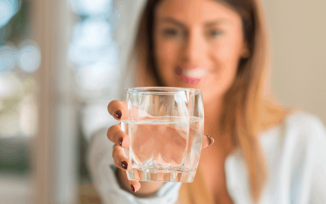 resilient woman holding a glass half full of water out to the camera, glass is in focus and background blurred